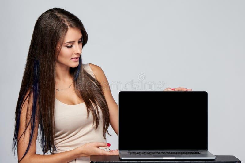 Женщина показывая пустой черный экран портативного компьютера стоковое изображение rf