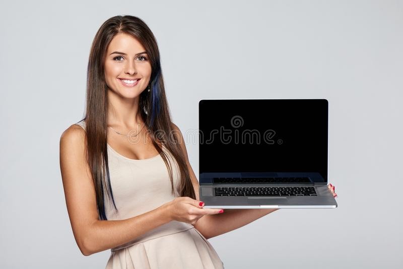 Женщина показывая пустой черный экран портативного компьютера стоковое фото rf