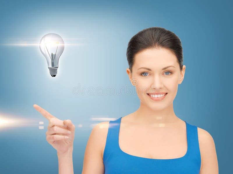 Женщина показывая электрическую лампочку на ее руке стоковое фото rf