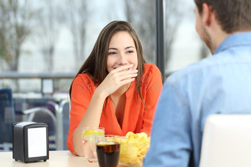 Женщина покрывая ее рот для того чтобы спрятать улыбку или дыхание стоковое фото rf