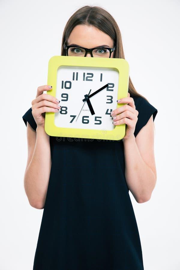 Женщина покрывая ее сторону с большими часами стоковое изображение