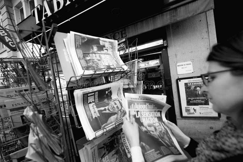 Женщина покупая международную прессу с Emmanuel Macron и морским пехотинцом стоковые изображения