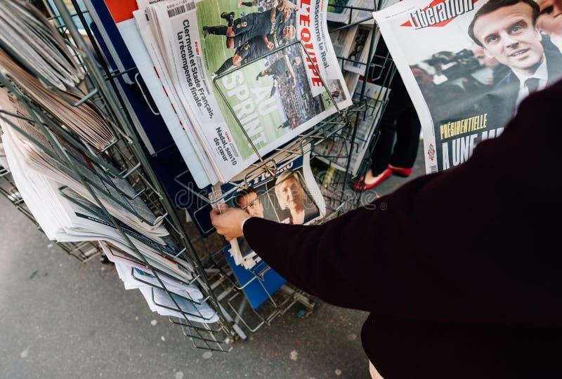 Женщина покупая международную прессу с Emmanuel Macron и морским пехотинцом стоковое фото