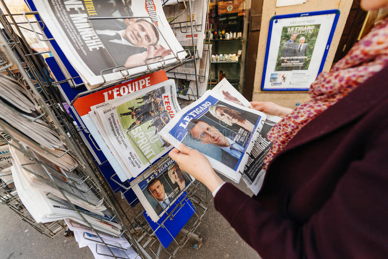 Женщина покупая международную прессу с Emmanuel Macron и морским пехотинцом стоковое изображение
