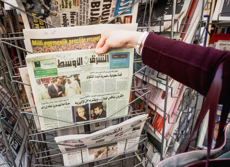 Женщина покупая международную прессу с Emmanuel Macron и морским пехотинцом стоковое фото rf