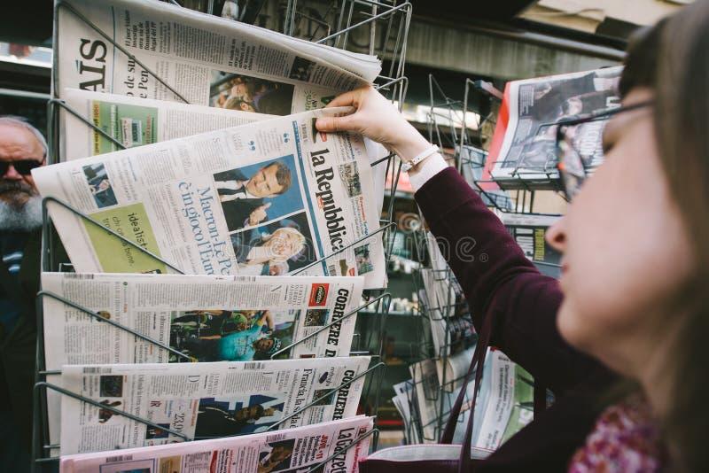 Женщина покупая международную прессу с Emmanuel Macron и морским пехотинцом стоковое изображение rf