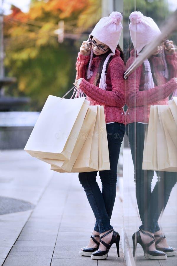 Женщина покупкы на телефоне стоковая фотография rf