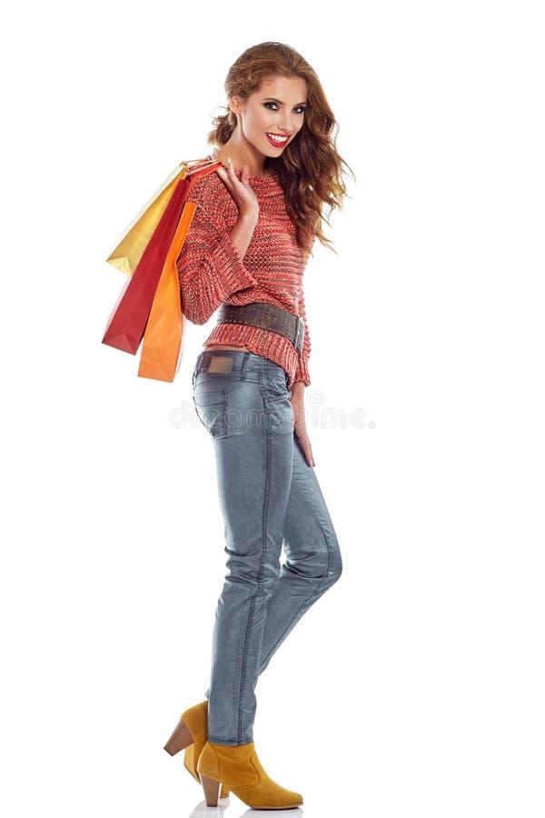 Женщина покупок держа сумки, изолированные на белизне стоковые изображения