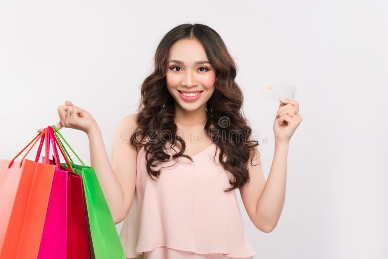 Женщина покупок при сумки показывая кредитную карточку изолированную на белизне стоковые фотографии rf