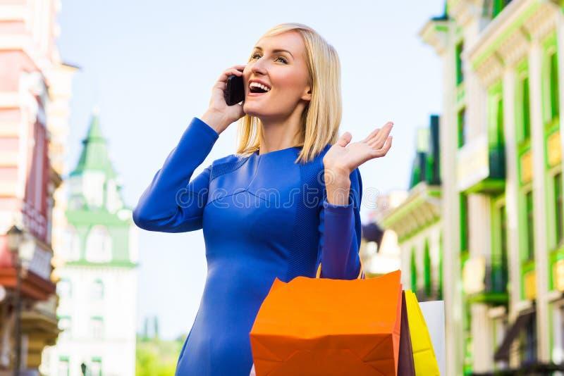 Женщина покупок с сумками говоря на телефоне внешнем стоковое изображение rf