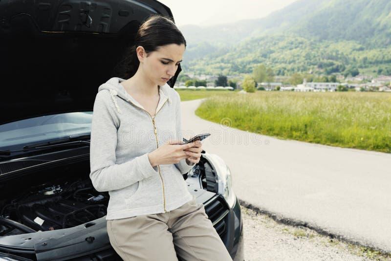 Женщина полагаясь на автомобиле и вызывая ремонтные услуги автомобиля стоковое изображение rf