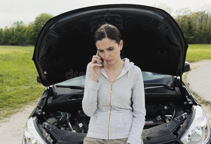 Женщина полагаясь на автомобиле и вызывая ремонтные услуги автомобиля стоковое фото