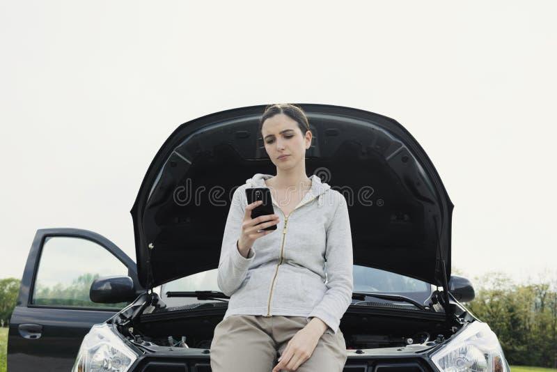Женщина полагаясь на автомобиле и вызывая ремонтные услуги автомобиля стоковая фотография