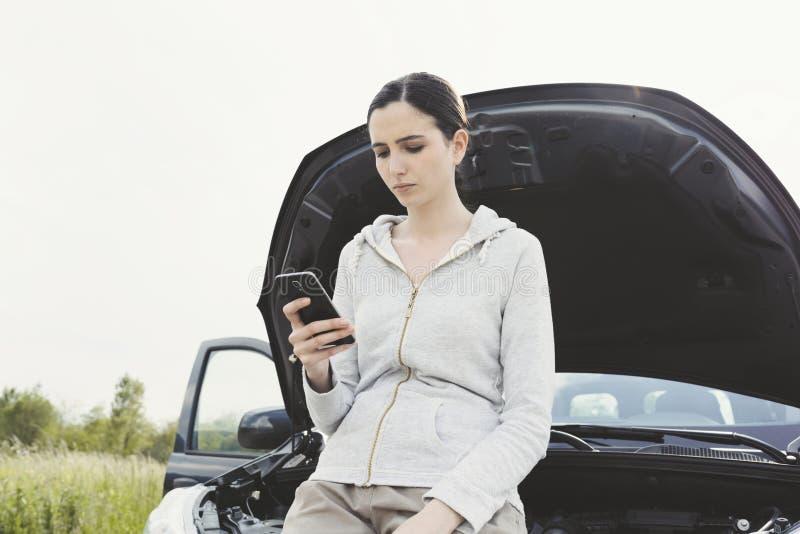 Женщина полагаясь на автомобиле и вызывая ремонтные услуги автомобиля стоковые фотографии rf