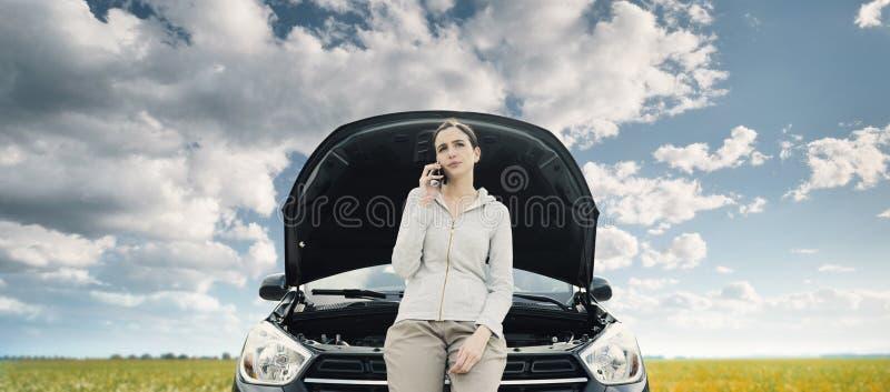 Женщина полагаясь на автомобиле и вызывая ремонтные услуги автомобиля стоковое изображение