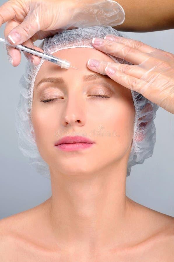Женщина получает впрыску в лбе Против старения обработка и подтяжка лица Косметические обработка и пластическая хирургия стоковые фотографии rf