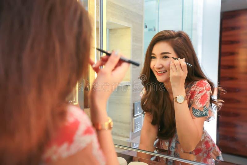 Женщина получая готовый для работы делая режим макияжа утра кладя тушь в bathroom стоковые изображения