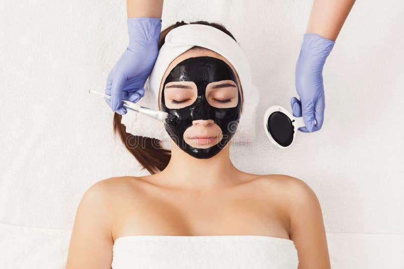 Женщина получая лицевой щиток гермошлема beautician на курорте стоковое изображение