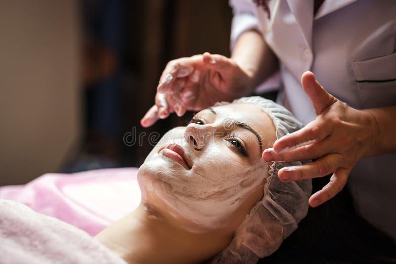Женщина получая лицевую маску шелушения заботы beautician на salo курорта стоковая фотография rf