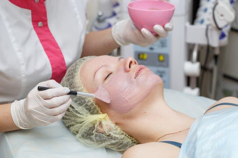 Женщина получая сторону слезая маску в салоне красоты спа стоковая фотография rf