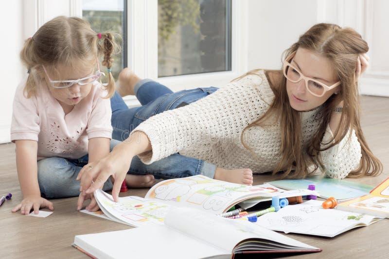 Женщина помогает ребенку нарисовать стоковое изображение