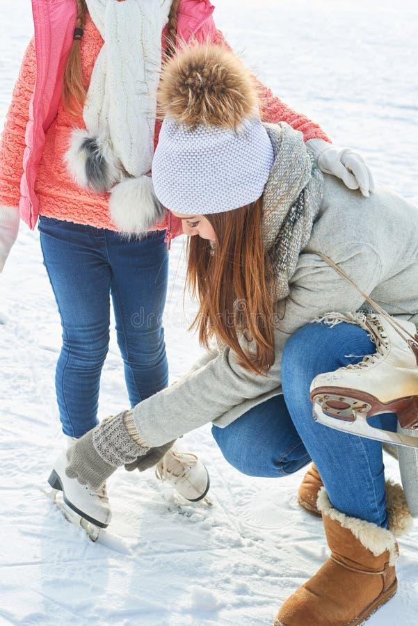 Женщина помогает ребенку с лед-коньками стоковое изображение