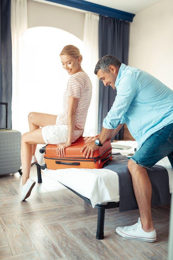 Женщина помогая ее супругу пакуя их чемодан стоковые фото