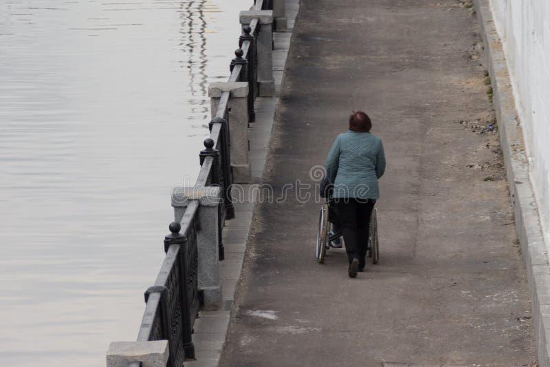 Женщина помогая свернуть кресло-коляску с человеком вдоль прогулки стоковое фото rf