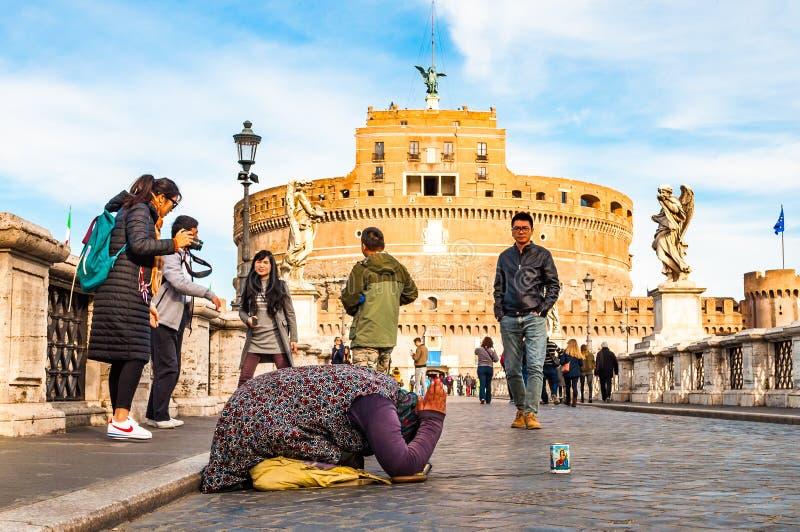 """Женщина попрошайки спрашивая милостыни на ее коленях на Ponte Sant """"Angelo, мосте Hadrian вполне идя людей с Castel Sant """"Angelo, стоковая фотография rf"""