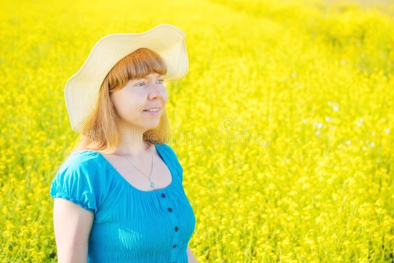 Женщина портрета в голубой прогулке платья и соломенной шляпы в желтом поле сурепки стоковые фото