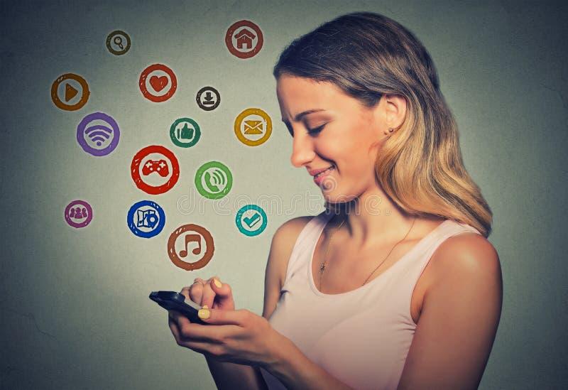 Женщина портрета используя app на умном телефоне стоковые изображения