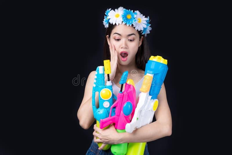 Женщина портрета красивая азиатская принимает пластиковое оружие на черной предпосылке партия водяного пистолета или фестиваль So стоковые фото