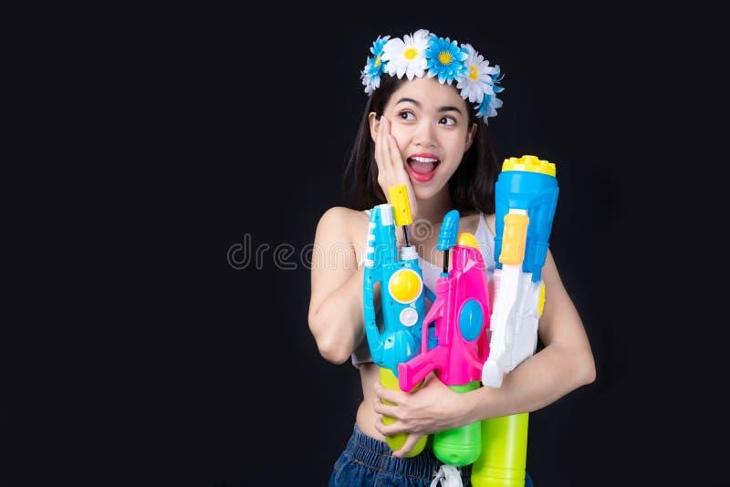 Женщина портрета красивая азиатская принимает пластиковое оружие на черной предпосылке партия водяного пистолета или фестиваль So стоковая фотография