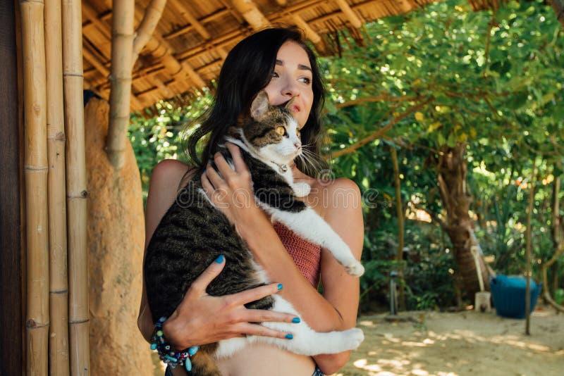 Женщина портрета красивая держа кота в ее nands Привлекательное брюнет с котами стоковые изображения
