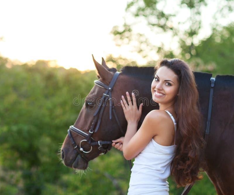 Женщина портрета красивая с лошадью длинных волос следующей стоковое фото rf