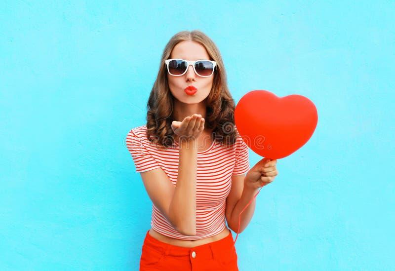 Женщина портрета милая посылает поцелуй воздуха с красной формой сердца воздушного шара над синью стоковая фотография