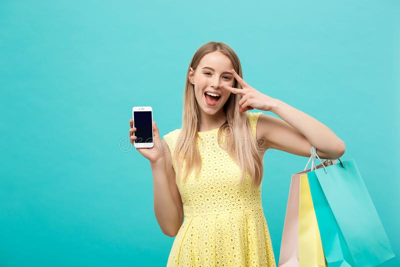Женщина портрета молодая привлекательная с хозяйственными сумками показывает экран ` s телефона сразу к камере Изолировано на син стоковое фото rf