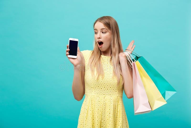 Женщина портрета молодая привлекательная с хозяйственными сумками показывает экран ` s телефона сразу к камере Изолировано на син стоковая фотография