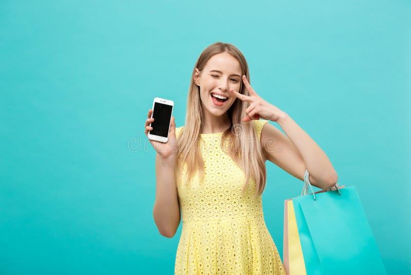 Женщина портрета молодая привлекательная с хозяйственными сумками показывает экран ` s телефона сразу к камере Изолировано на син стоковые изображения rf