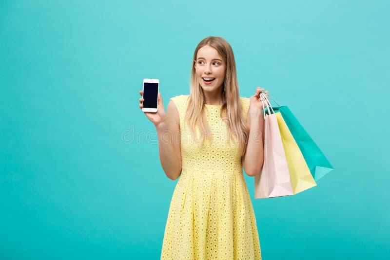 Женщина портрета молодая привлекательная с хозяйственными сумками показывает экран ` s телефона сразу к камере Изолировано на син стоковые изображения