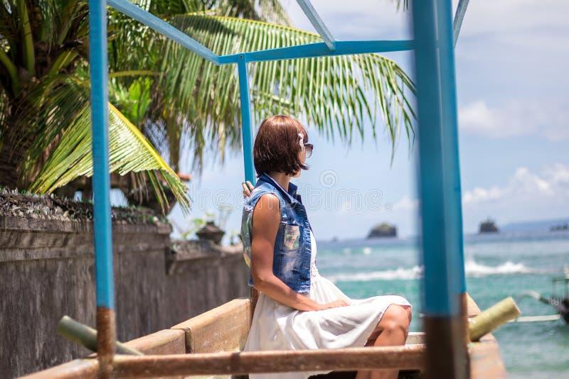 Женщина портрета молодая красивая тропическая на летних каникулах в Азии, Бали Ослабляющ на тропическом пляже, ландшафт моря и стоковое изображение rf