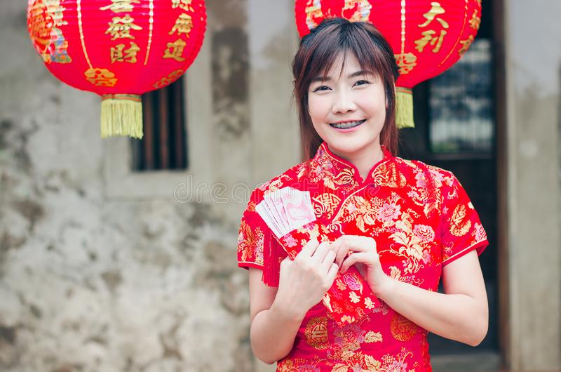 Женщина портрета очаровательная красивая азиатская носит cheongsam для того чтобы одевать для открытия красного конверта с деньга стоковое изображение rf