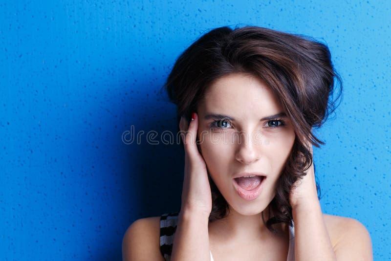 Женщина портрета привлекательная на голубой предпосылке стоковые фотографии rf