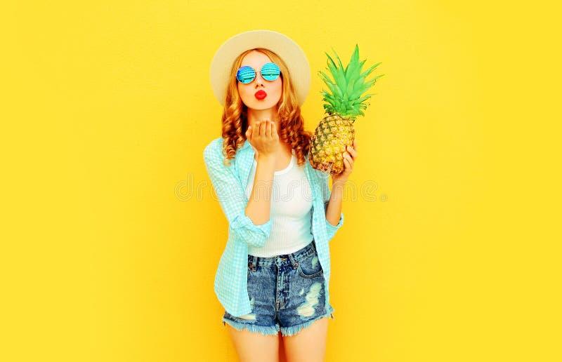 Женщина портрета с ананасом отправляя сладкий поцелуй воздуха в соломенной шляпе лета, солнечных очках, шортах на красочном желто стоковое изображение rf