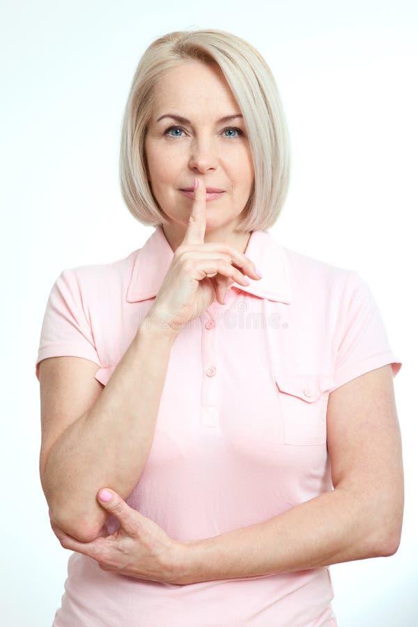 Женщина портрета с пальцем на губах, или секретный знак руки жеста изолированный на белой предпосылке стоковая фотография rf