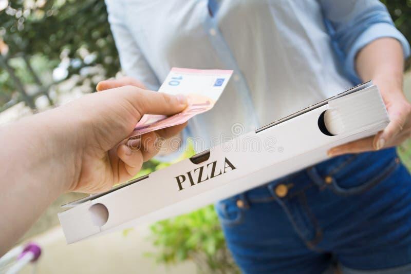 Женщина поставляя пиццу стоковое изображение