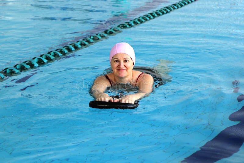 Женщина постаретая серединой в бассейне стоковое изображение rf