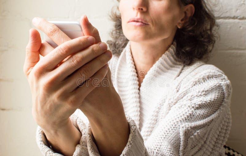 Женщина постаретая серединой держа телефон стоковая фотография