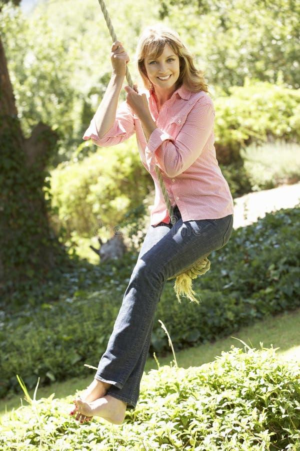 Женщина постаретая серединой имея потеху на качании веревочки стоковые фотографии rf