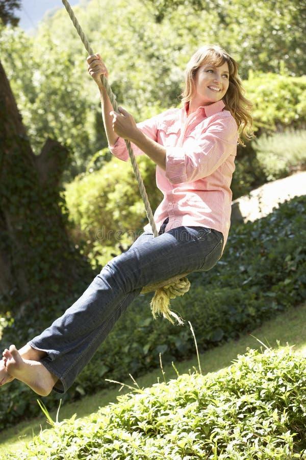 Женщина постаретая серединой имея потеху на качании веревочки стоковые изображения rf